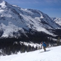 Ben Pope skiing towards the forested valley with Deadwood Peak in the backdrop