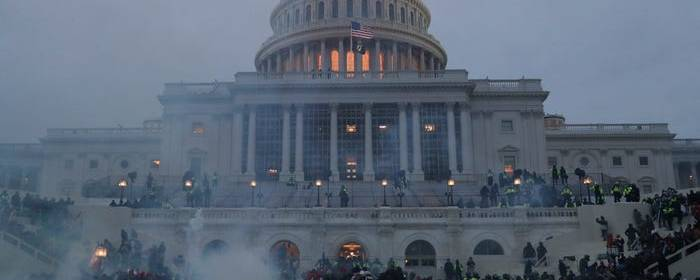 The US Capitol Building. Smoke smolders in front of it. Behind it is a grey sky.