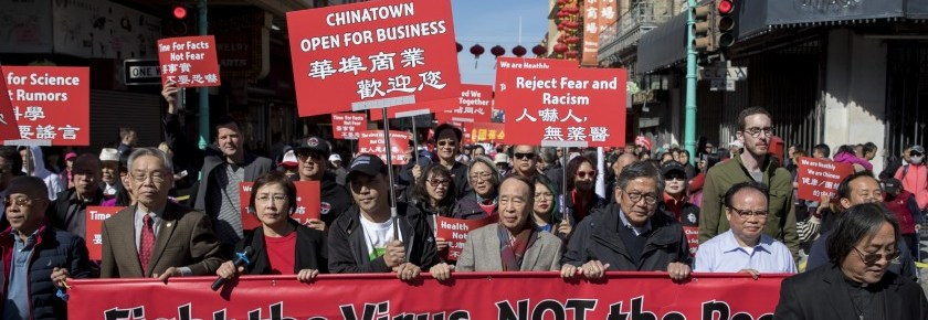 Hundreds of residents of San Francisco's Chinatown hold red signs and march to protest discrimination against the Chinese community.