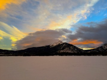Low clouds and sun light up the sky over Peak 1.