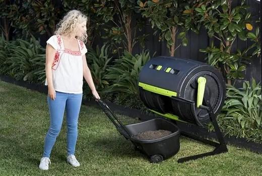 Woman using a compost tumbler bin
