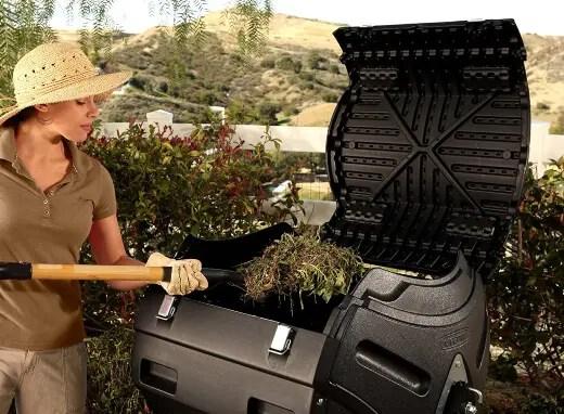 Woman using tumbling composting bins
