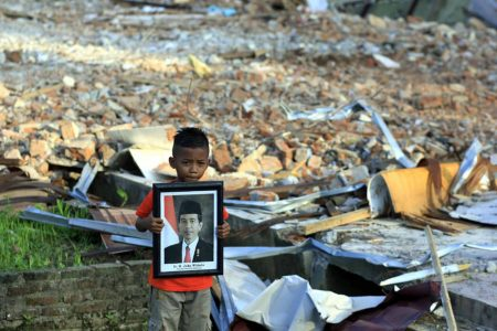 Muhammad Raja (11) memegang foto Presiden Joko Widodo di bangunan sekolahnya. Foto itu selamat akibat gempa 6,5 SR, Rabu 7 Desember lalu, sementara sekolahnya SD Negeri Tampui, Pidie Jaya, hancur.  ENO SUNARNO/RAKYAT ACEH