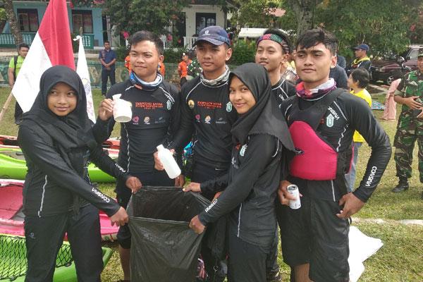Tim Ekspedisi Kayak Pelajar Indonesia URaL SMAN 28 Jakarta menunjukkan kantong plastik berisikan sampah yang mereka kutip dari perairan Danau Toba.