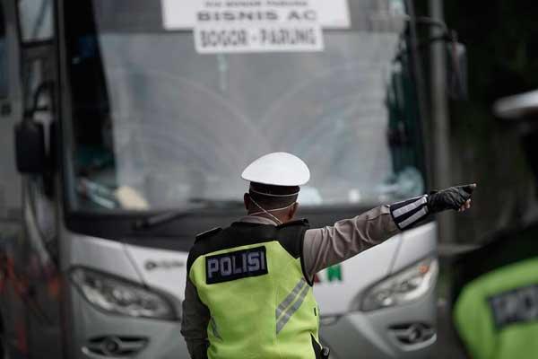 PUTAR BALIK Personel Polda Metro Jaya mengalihkan bus keluar tol Cikarang Barat di jalan tol Cikampek, Bekasi, Jawa Barat, Jumat (24/4). Buntut larangan mudik yang ditetapkan pemerintah, ribuan kendaraan disuruh memutar balik kembali ke asal. Poldasu juga akan menerapkan kebijakan yang sama.