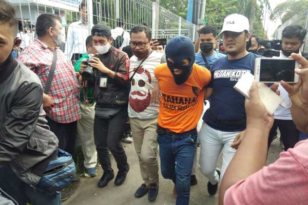 DITANGKAP: Tersangka Ramadsyah pakai tutup kepala digiring Personel Satreskrim  Poltabes Medan setelah ditangkap dari tempat persembuyianya di Delitua, Kabupaten Deliserdang. M IDRIS/sumut pos.