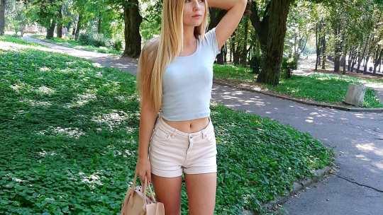 Блондинка позирует  в парке в белой майке с сумочкой.