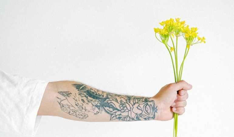 crop man with flower in hand
