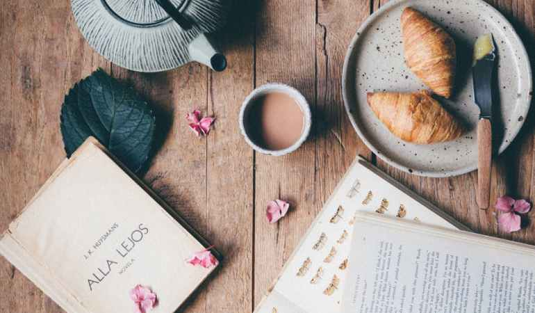 photo of opened books near croissants