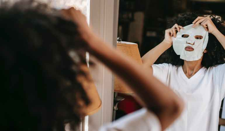 black young female putting sheet mask while standing against mirror