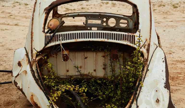 abandoned broken car in sandy terrain