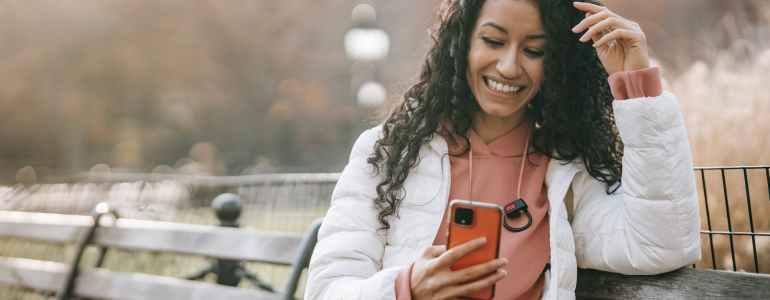 cheerful latin american woman with smartphone