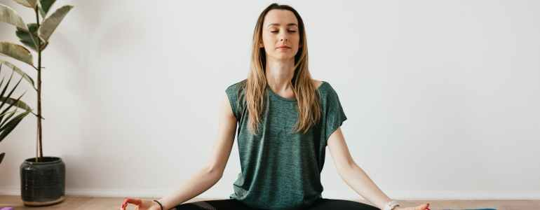 peaceful lady sitting in padmasana pose while meditating on mat