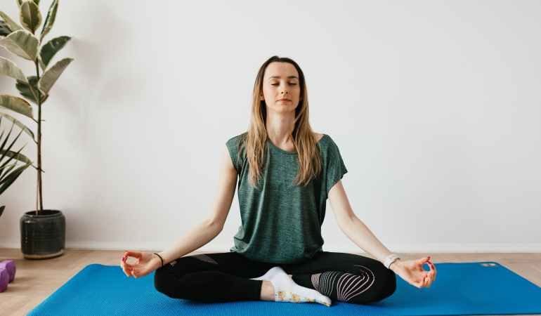 peaceful lady sitting in padmasana pose while meditating on mat