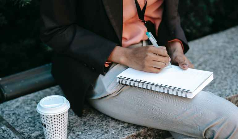 ethnic woman writing notes in planner with takeaway coffee