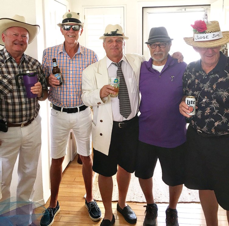 Men showing off their hats and attire at Kentucky Derby innovative party