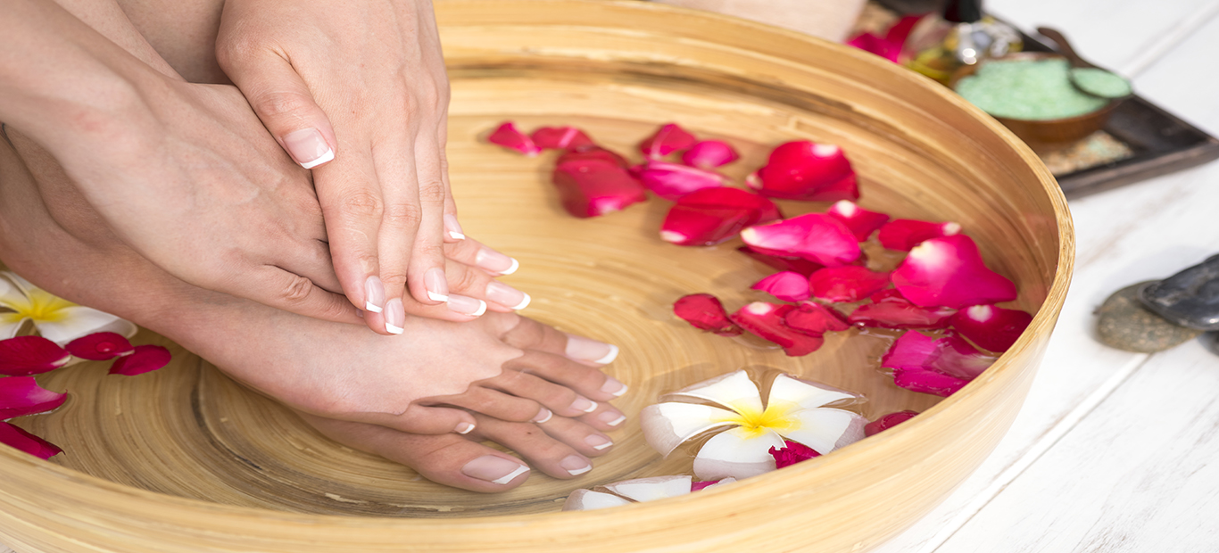 Closeup photo of a female feet at spa salon, Female legs in water decoration the flowers.