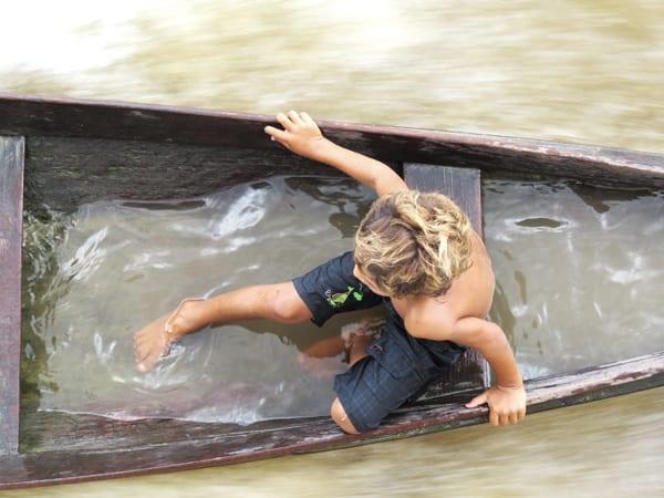 Menino esperando na canoa, enquanto seu pai sobe no barco para vender camarão