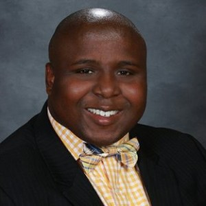 A headshot of Gaven Norris in college (2007-2011), a black man wearing a dark suit jacket and a bow tie with a button up shirt