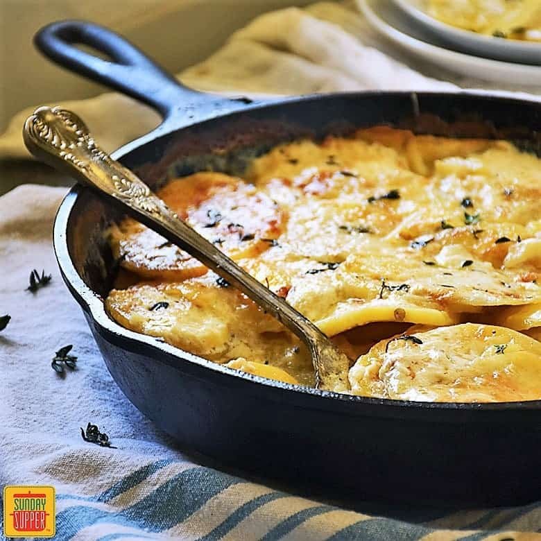 Gluten free au gratin potatoes in a skillet with a serving spoon
