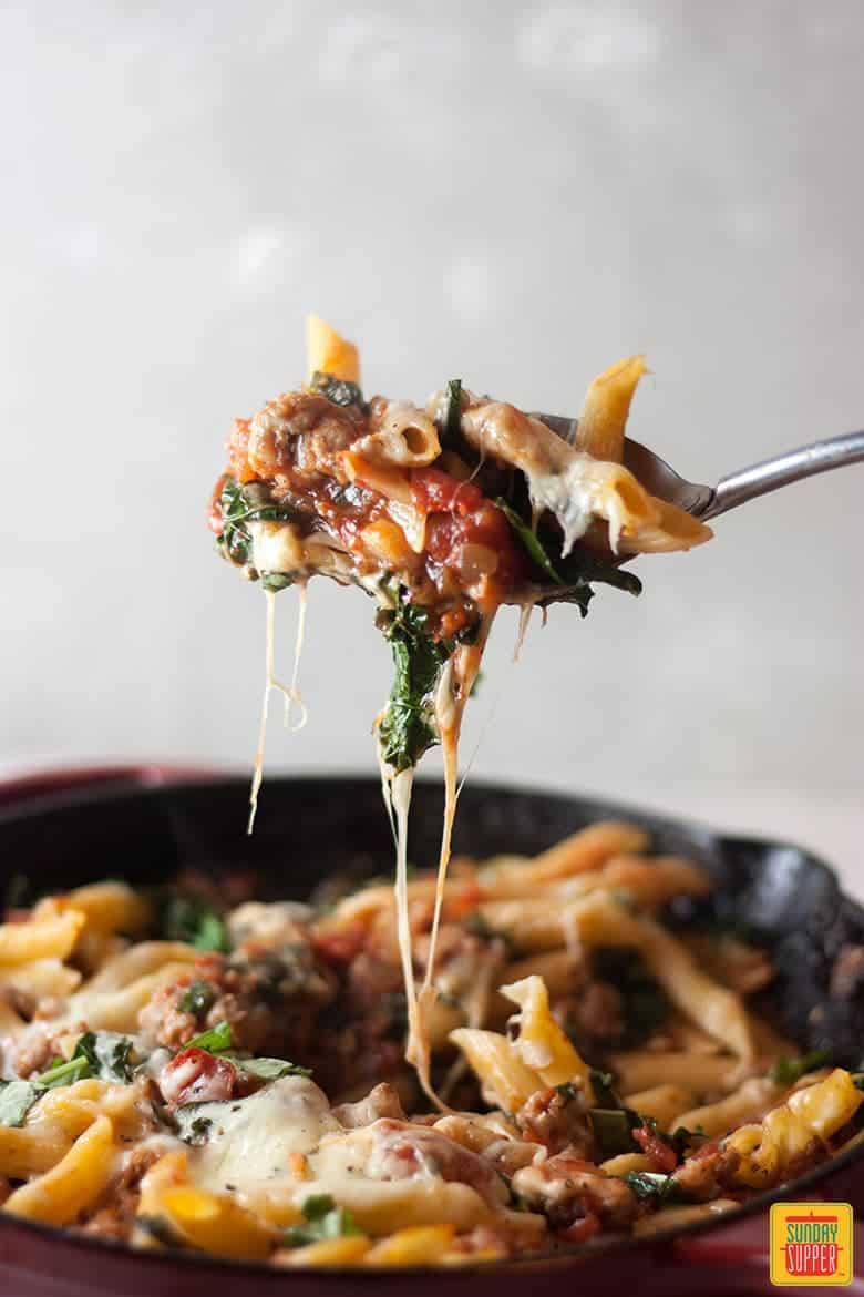 Big cheesy spoonful of sausage and kale pasta eaten right out of the skillet!
