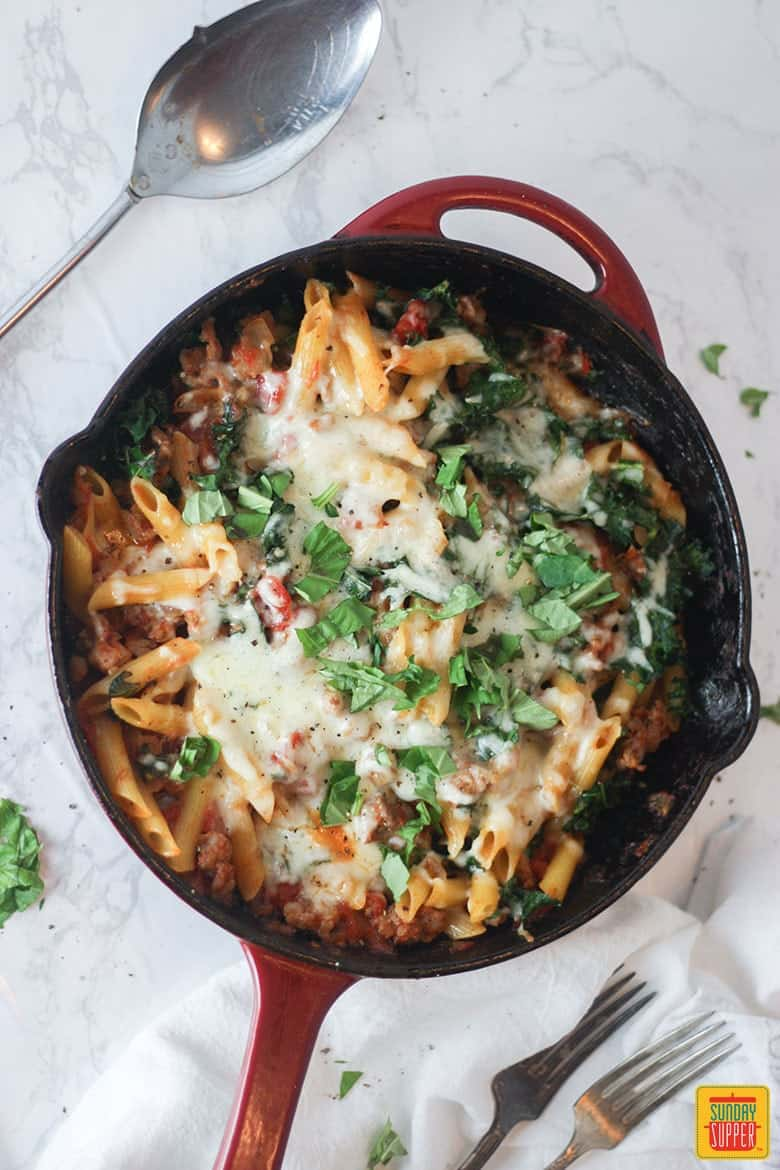 Skillet with baked sausage and kale pasta ready to eat