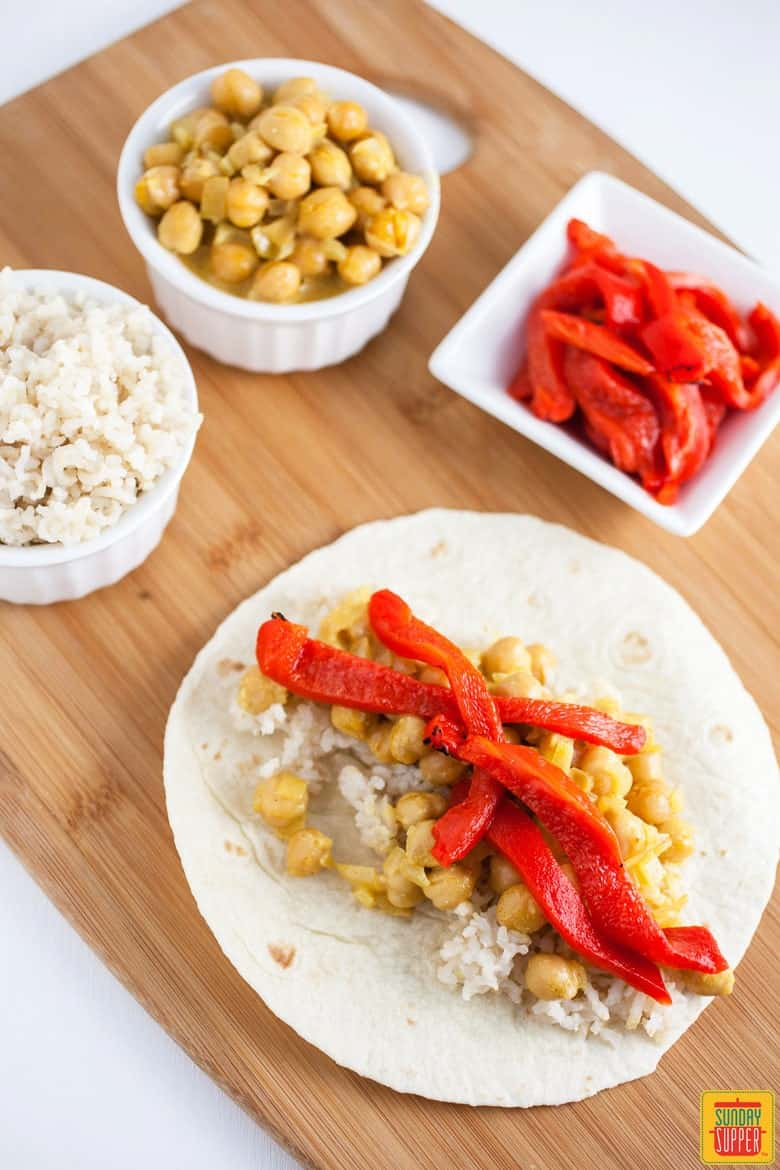 Rice, Chickpea Curry, and Roasted Red Peppers being assembled on a tortilla for our Vegetarian Enchiladas Recipe