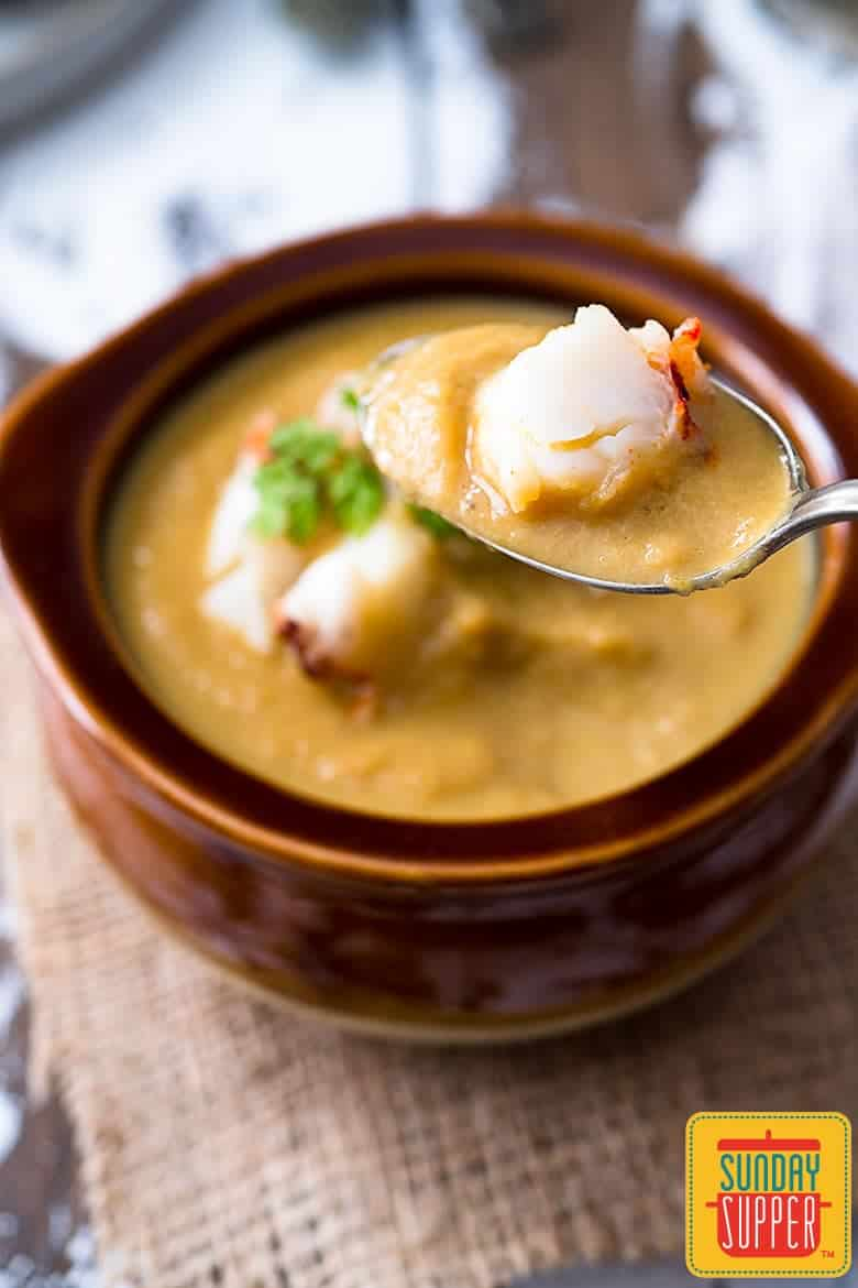 Spoon holding celery root soup with a piece of buttery lobster ready to eat