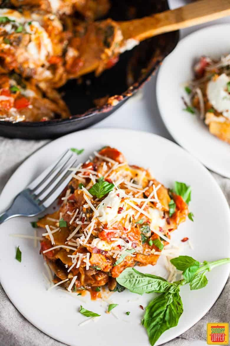 Cast Iron Skillet Lasagna served on a white plate garnished with fresh basil