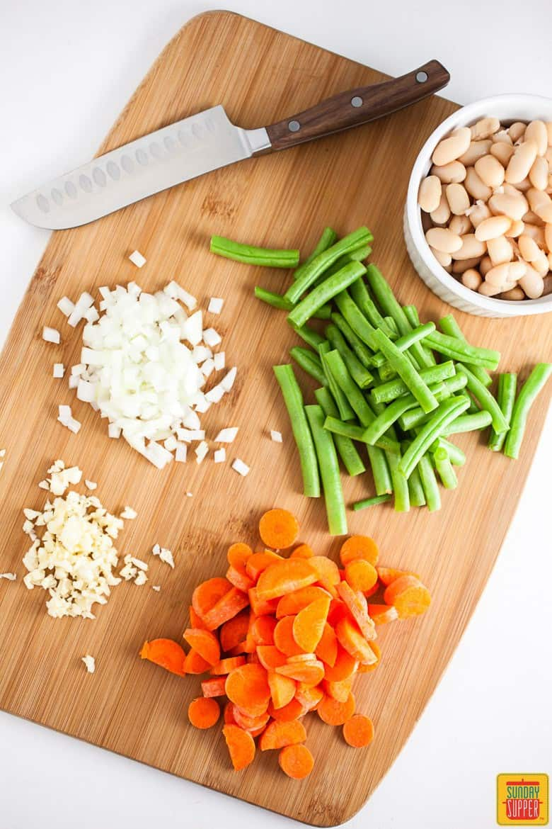Cutting board topped with chopped vegetables for the Italian Vegetable Soup and Pesto Grilled Cheese recipe