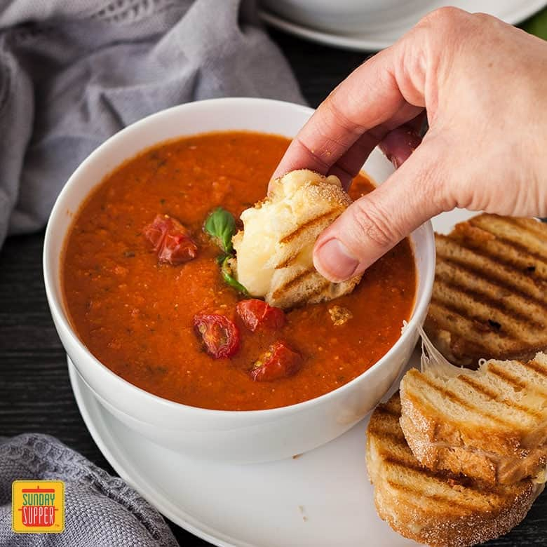 Dipping mini grilled cheese sandwich into a bowl of roasted tomato soup