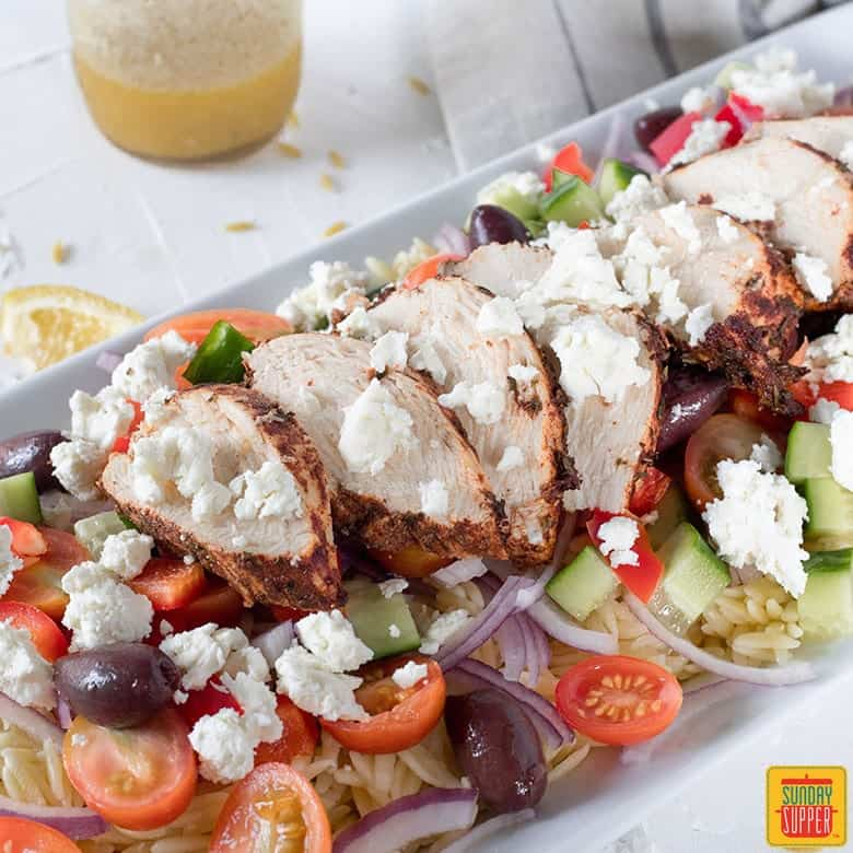 plate of oven baked greek chicken on bed of orzo and greek salad