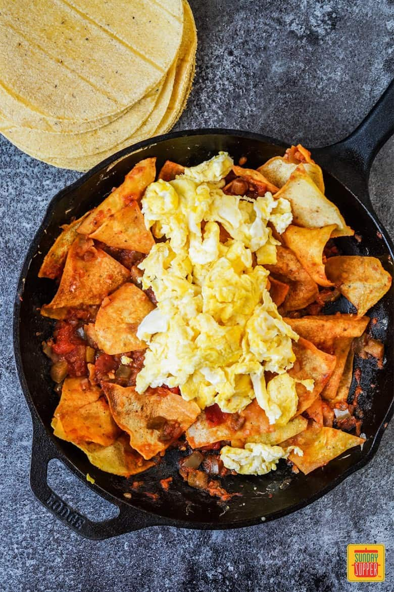 Adding eggs to Chilaquiles Rojos