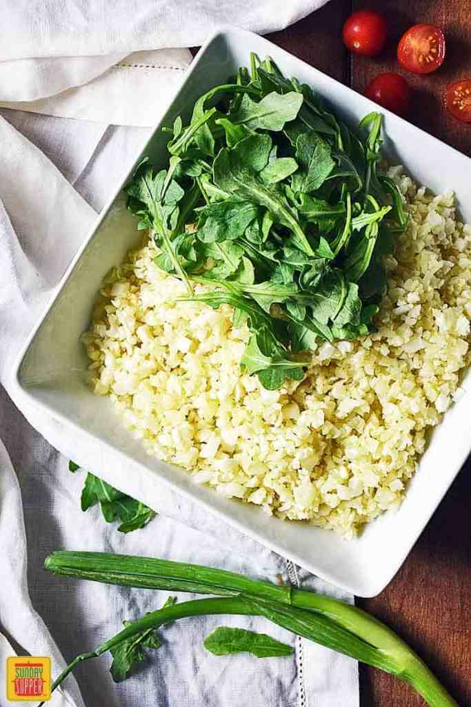 Assembling the Cauliflower Rice Salad starting with baby arugula on top of the cauliflower rice