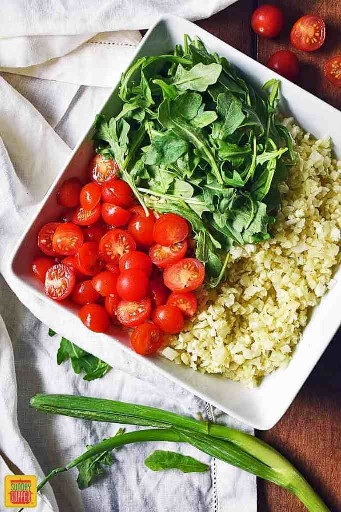 Assembling the Cauliflower Rice Salad with baby arugula and halved tomatoes on top of the cauliflower rice