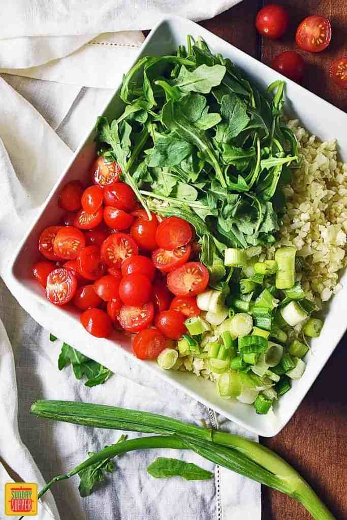 Assembling the Cauliflower Rice Salad with baby arugula, halved tomatoes, and green onions on top of the cauliflower rice
