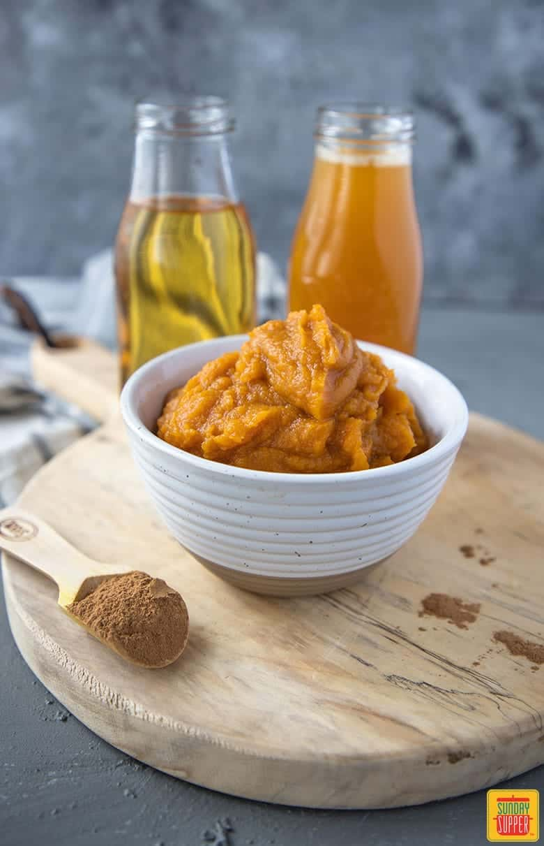 pumpkin juice recipe ingredients - bowl of pumpkin puree, teaspoon of spice mixture and two bottles of apple juice and peach nectar