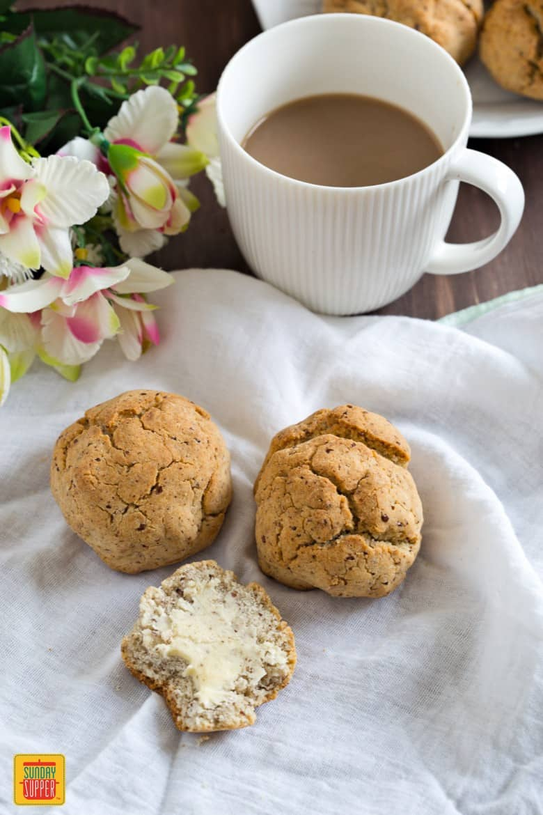 gluten free rolls on a napkin with a white cup of coffee and flowers on the side