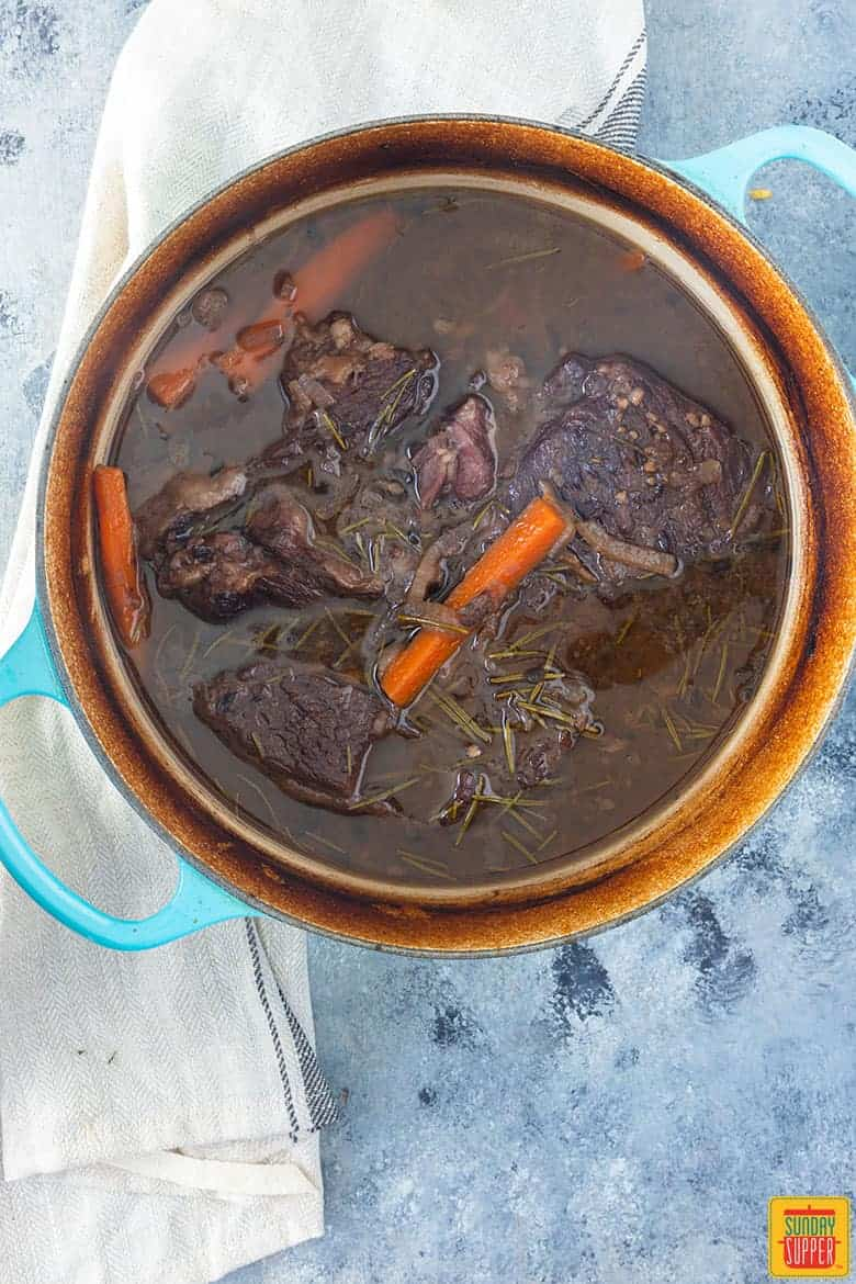 cooked dutch oven pot roast in blue dutch oven