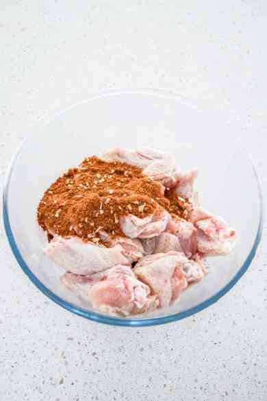 Raw chicken wings in a bowl ready to mix with seasonings for slow cooker wings