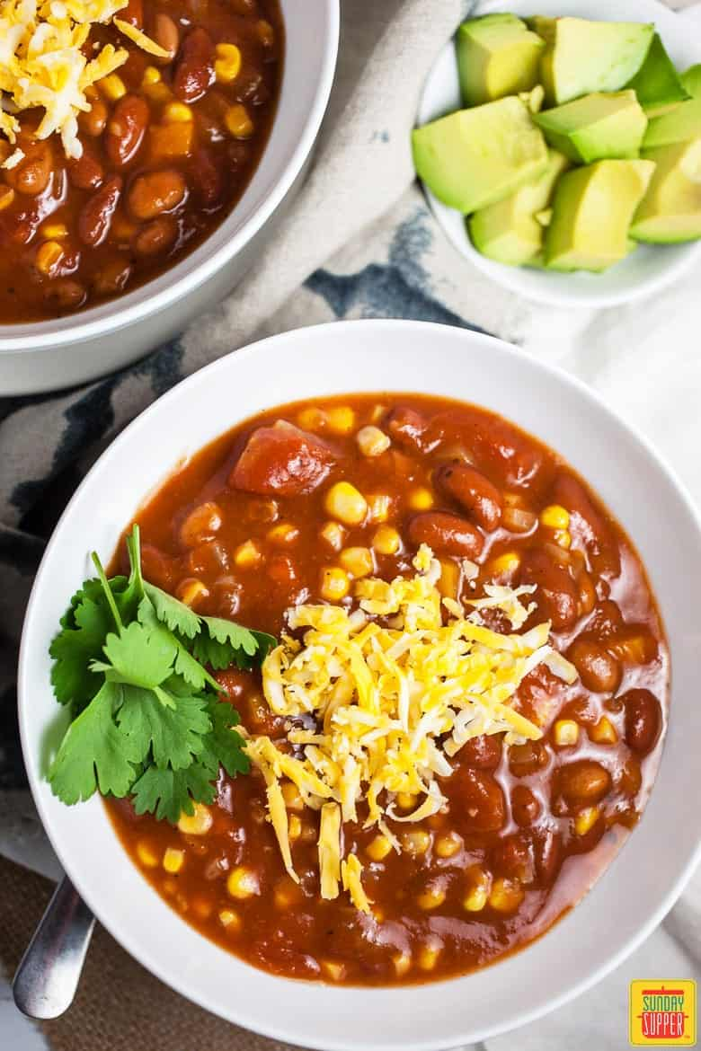 2 white bowls loaded with Slow Cooker Vegetarian Chili, shredded cheese, & garnished with cilantro. A side of avocado is nearby