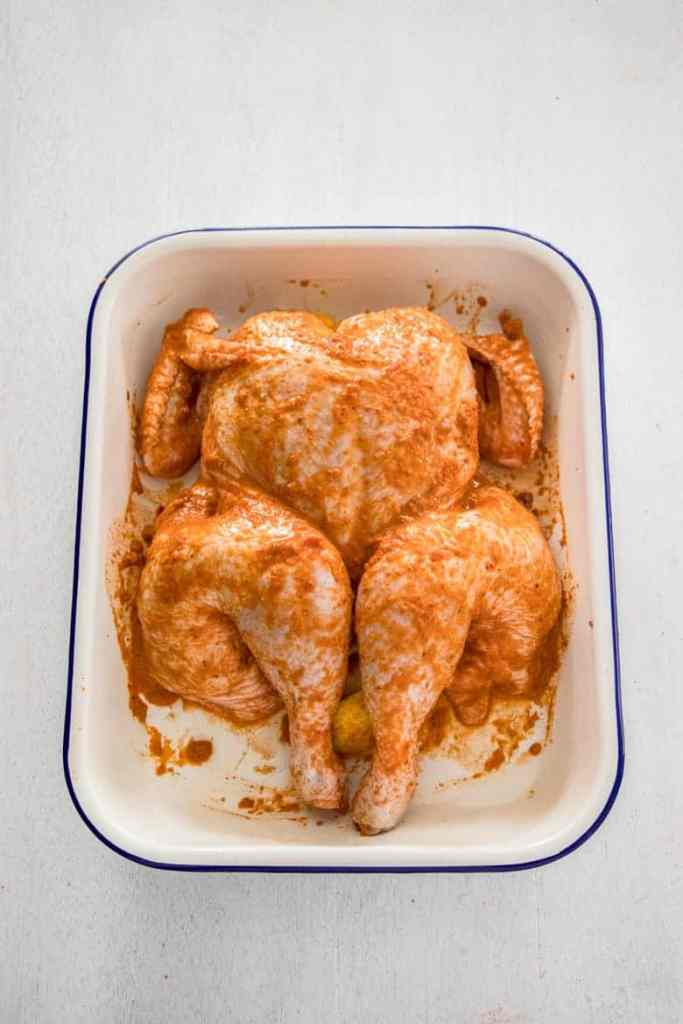 a whole chicken in a baking dish covered with peri peri sauce