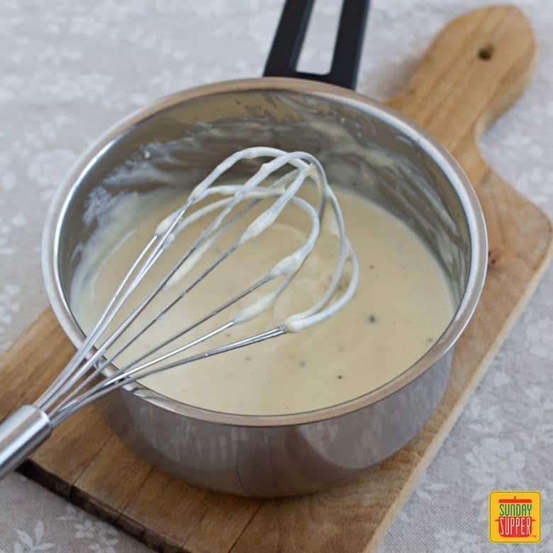 How to make Cheese Sauce: cheese sauce in a saucepan with a whisk