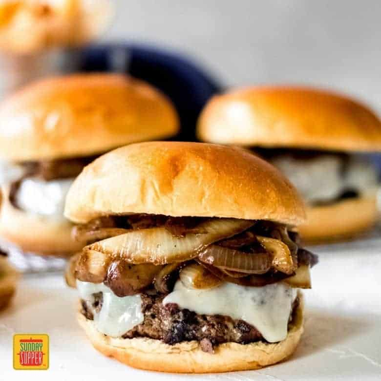 Three Mushroom Swiss Burgers on a white surface