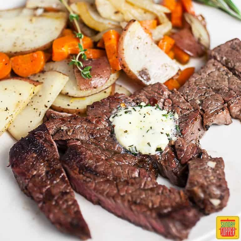 Grilled chuck steak served with potatoes and carrots and a compound butter on a white surface
