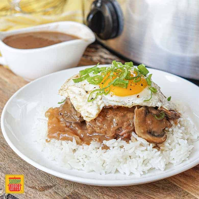 Slow Cooker Beef Gravy with Loco Moco on a white plate