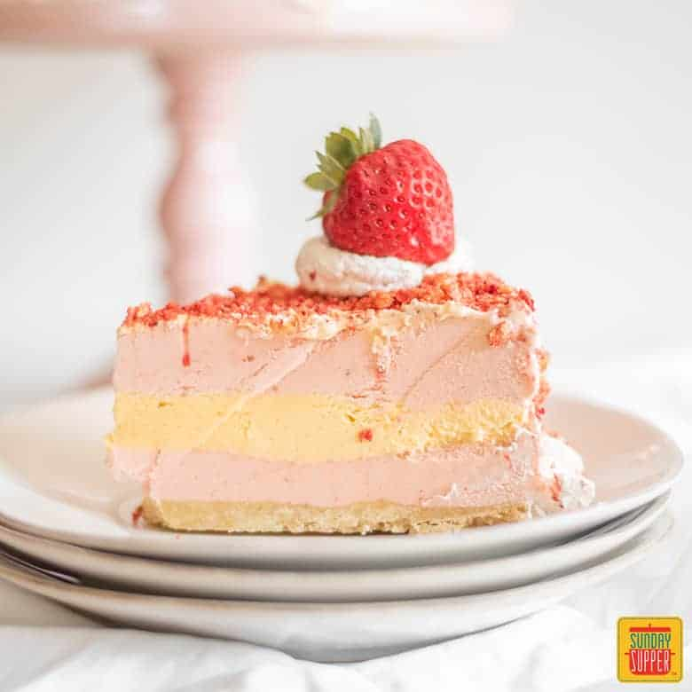 Strawberry shortcake ice cream cake slice on white plate with fresh strawberry topping