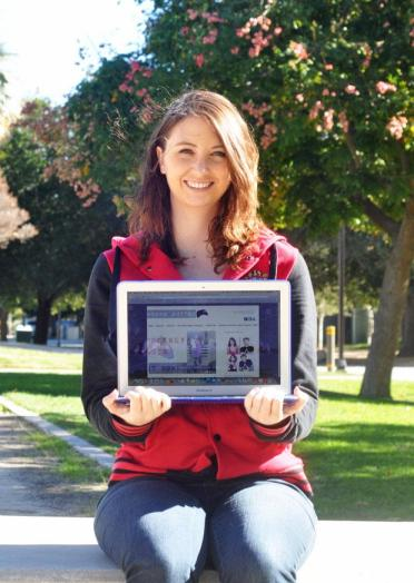 CSUN student Emily Kelley holds up her award-winning website on her laptop. Photo credit: Lisa Anderson / Daily Sundial