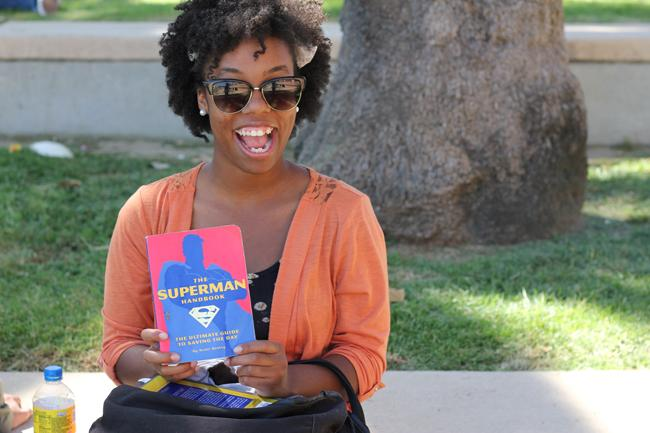 """Brittney Harvey, freshman deaf studies major, shows off her beloved """"How to Be Superman"""" book. Photo credit by Brionna Lewis."""