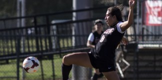 Women CSUN student maintains to keep the soccer ball balanced away from opposing team at Long Beach State University.